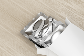 White box with three condoms inside on wooden table