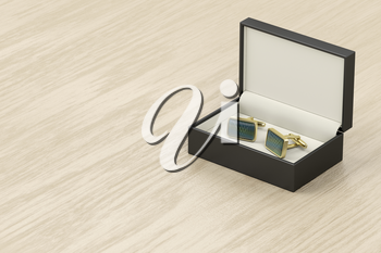 Box with golden cufflinks on wooden table
