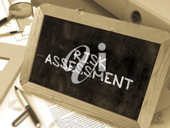 Handwritten Risk Assessment on a Chalkboard. Composition with Chalkboard and Ring Binders, Office Supplies, Reports on Blurred Background. Toned Image. 3D Render.