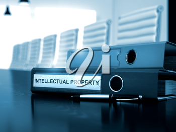 Office Binder with Inscription Intellectual Property on Office Desktop. Intellectual Property - Illustration. Toned Image. 3D Render.