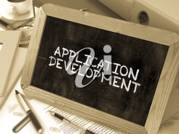 Application Development Handwritten on Chalkboard. Composition with Small Chalkboard on Background of Working Table with Office Folders, Stationery, Reports. Blurred, Toned Image. 3D Render.