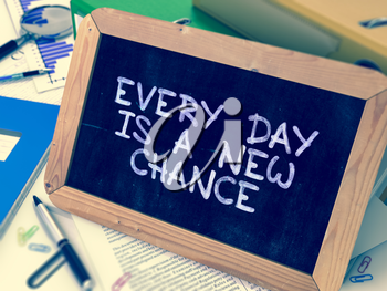 Every Day is a New Chance Handwritten on Chalkboard. Composition with Small Chalkboard on Background of Working Table with Ring Binders, Office Supplies, Reports. Blurred, Toned Image. 3D Render.