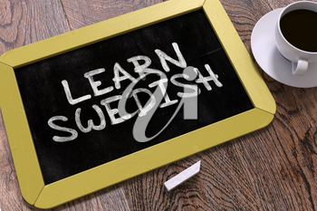 Hand Drawn Learn Swedish Concept  on Small Yellow Chalkboard. Business Background. Top View.