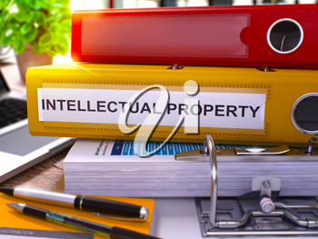 Yellow Office Folder with Inscription Intellectual Property on Office Desktop with Office Supplies and Modern Laptop. Intellectual Property Business Concept on Blurred Background. 3D Render.