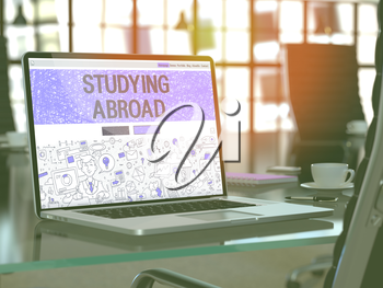 Modern Workplace with Laptop Showing Landing Page in Doodle Design Style with Text Studying Abroad. Toned Image with Selective Focus. 3D Render.