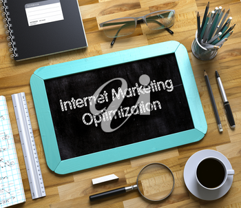 Top View of Office Desk with Stationery and Mint Small Chalkboard with Business Concept - Internet Marketing Optimization. Small Chalkboard with Internet Marketing Optimization. 3d Rendering.