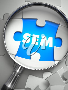 SEM - Search Engine Marketing - Word on the Place of Missing Puzzle Piece through Magnifier. Selective Focus.