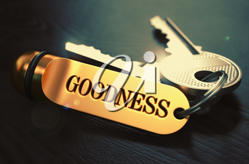 Keys and Golden Keyring with the Word Goodness over Black Wooden Table with Blur Effect. Toned Image.