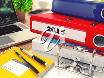 2015 - Red Office Folder on Background of Working Table with Stationery, Laptop and Reports. Business Concept on Blurred Background. Toned Image.