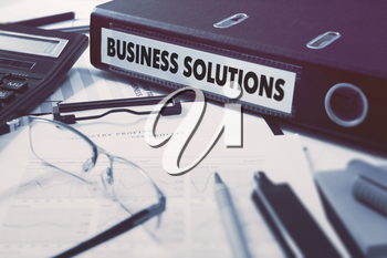 Ring Binder with inscription Business Solutions on Background of Working Table with Office Supplies, Glasses, Reports. Toned Illustration. Business Concept on Blurred Background.