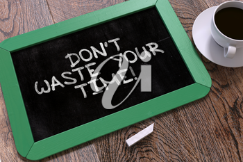 Don't Waste Your Time - Motivational Quote Hand Drawn on Green Chalkboard on Wooden Table. Business Background. Top View.