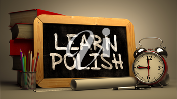 Learn Polish - Chalkboard with Hand Drawn Text, Stack of Books, Alarm Clock and Rolls of Paper on Blurred Background. Toned Image.