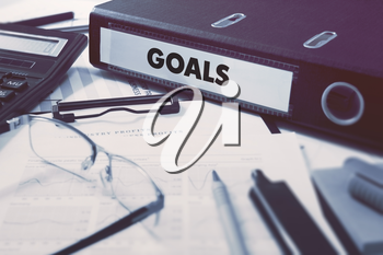 Goals - Office Folder on Background of Working Table with Stationery, Glasses, Reports. Business Concept on Blurred Background. Toned Image.