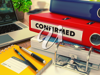 Red Office Folder with Inscription Confirmed on Office Desktop with Office Supplies and Modern Laptop. Business Concept on Blurred Background. Toned Image.