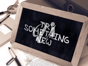 Try Something New - Inspirational Quote Handwritten on Chalkboard. Composition with Small Chalkboard on Background of Working Table with Ring Binders, Office Supplies, Reports. Blurred, Toned Image.