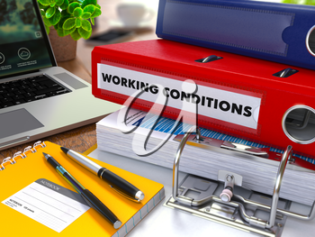 Red Ring Binder with Inscription Working Conditions on Background of Working Table with Office Supplies, Laptop, Reports. Toned Illustration. Business Concept on Blurred Background.