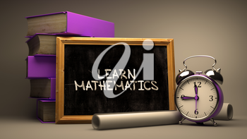Learn Mathematics - Chalkboard with Hand Drawn Text, Stack of Books, Alarm Clock and Rolls of Paper on Blurred Background. Toned Image.