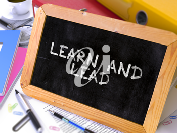 Learn and Lead - Chalkboard with Hand Drawn Motivation Quote, Stack of Office Folders, Stationery, Reports on Blurred Background. Toned Image.