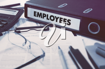 Ring Binder with inscription Employees on Background of Working Table with Office Supplies, Glasses, Reports. Toned Illustration. Business Concept on Blurred Background.