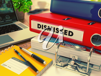 Red Office Folder with Inscription Dismissed on Office Desktop with Office Supplies and Modern Laptop. Business Concept on Blurred Background. Toned Image.