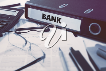 Bank - Office Folder on Background of Working Table with Stationery, Glasses, Reports. Business Concept on Blurred Background. Toned Image.