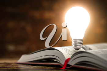 Light bulb on the  open book. Idea and creativity concept background. 3d illustration