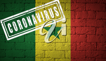 Flag of the Senegal on brick wall texture. stamped of Coronavirus. Corona virus concept. On the verge of a COVID-19 or 2019-nCoV Pandemic. Novel Chinese Coronavirus outbreak