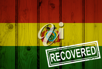 flag of Bolivia that survived or recovered from the infections of corona virus epidemic or coronavirus. Grunge flag with stamp Recovered