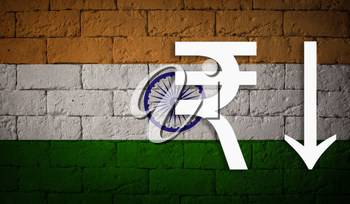symbolic depreciation of the national currency Rupee against of the country flag of India. Concept of depreciation of currency, economy fall and the breakdown of economic ties