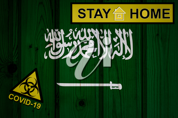 Flag of the Saudi Arabia in original proportions. Quarantine and isolation - Stay at home. flag with biohazard symbol and inscription COVID-19.
